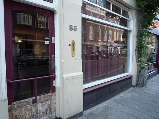 Dit is een voorbeeld van een gevel met een raamkozijn en een deur waar veel gaten en scheuren in zaten.